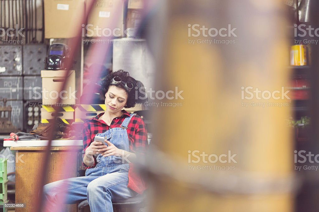 Young woman using smart phone, sitting in a weld workshop stock photo
