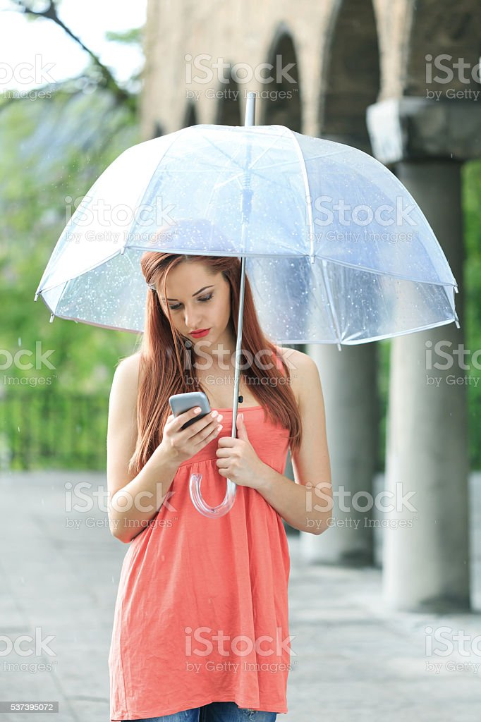 Young woman using smart phone under the rain stock photo