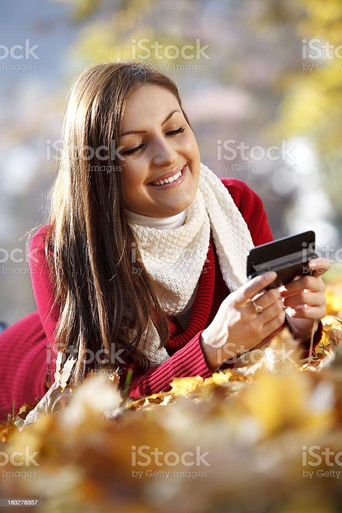 Young woman using smart phone while enjoying autumn royalty-free stock photo