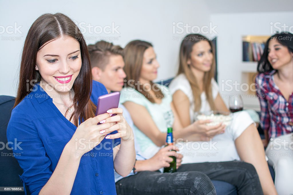 Young woman using smart phone while sitting with her friends. stock photo