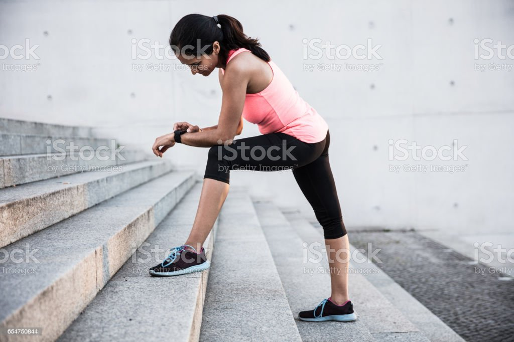 Young woman using smart watch for the running in the city. stock photo