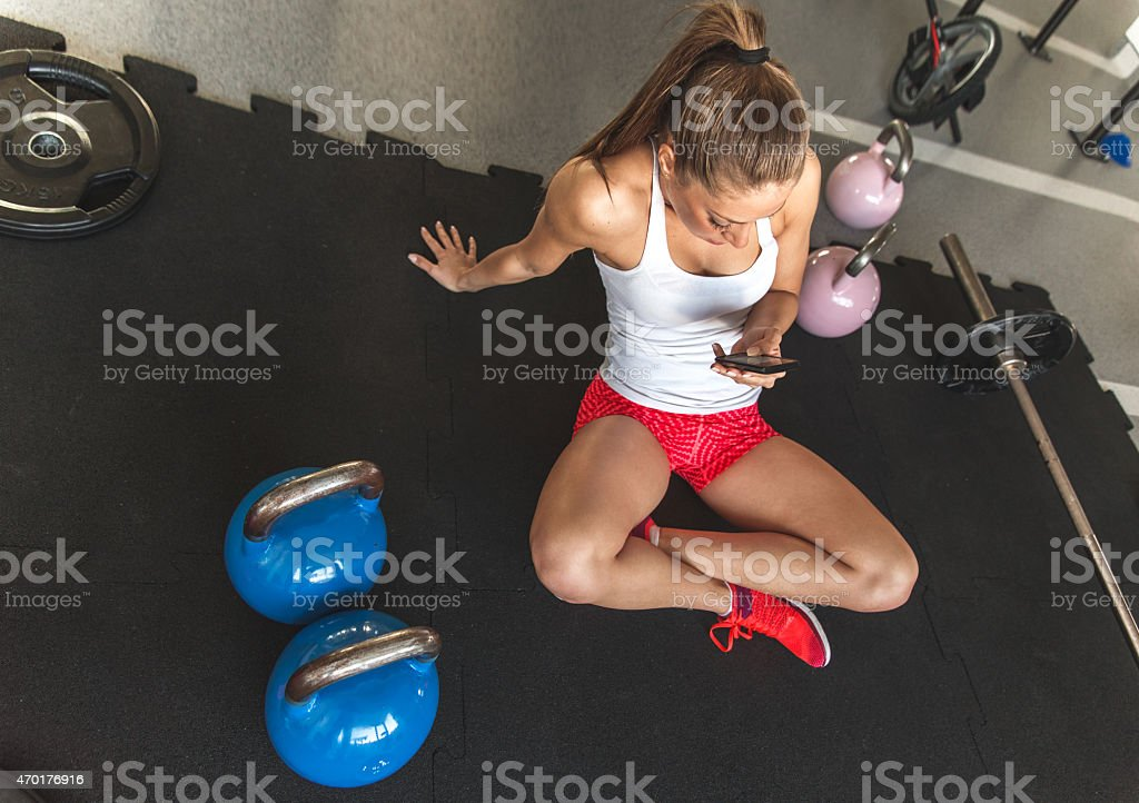 Young woman using smartphone at the gym stock photo