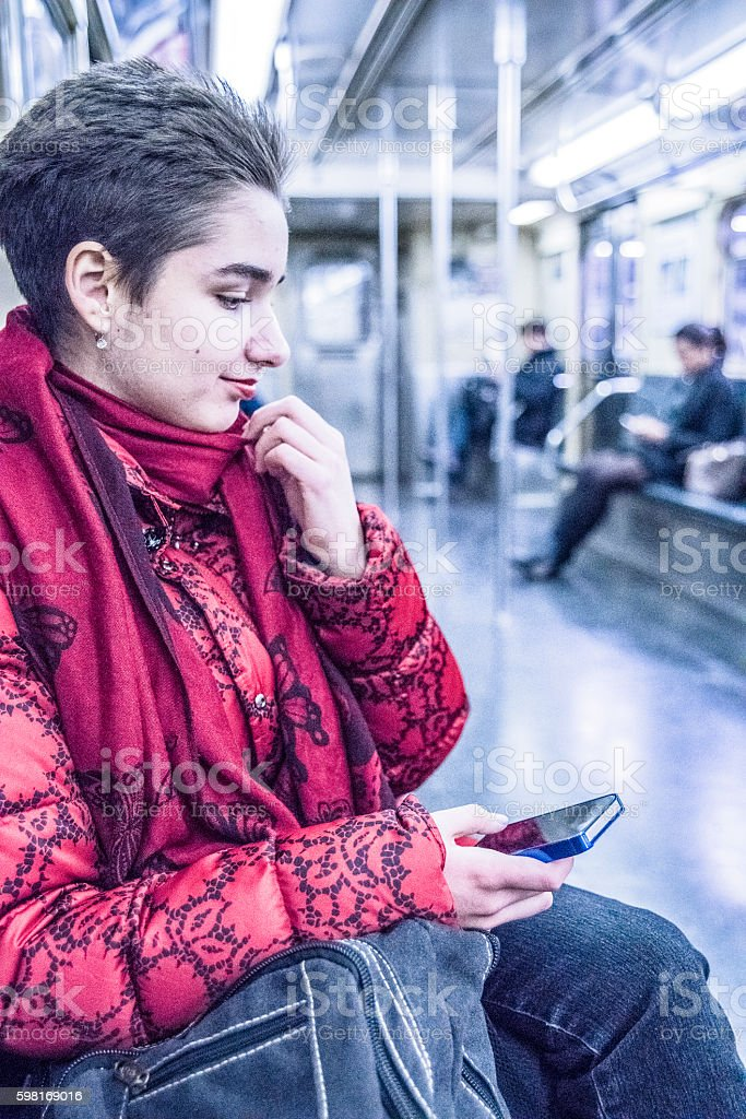 Young woman using smartphone in subway, New York City stock photo