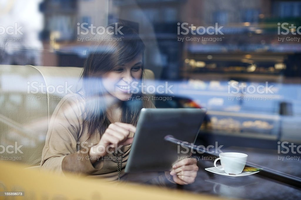 Young woman using tablet in coffee shop royalty-free stock photo