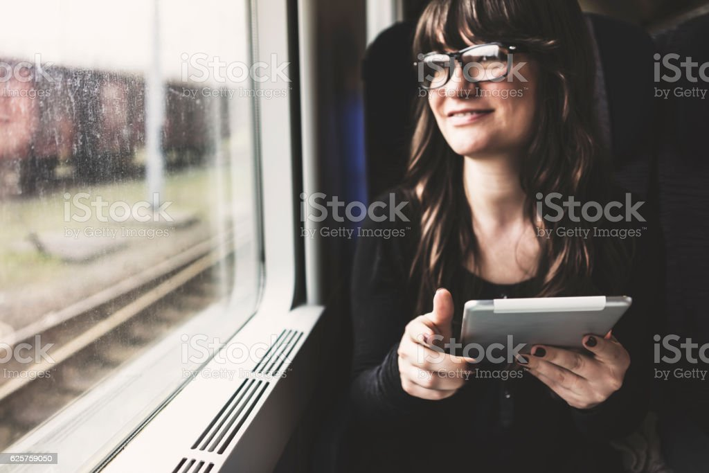 Young woman using tablet pc in train, travelling stock photo