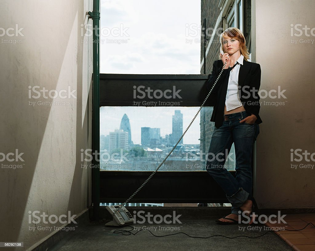 Young woman using telephone in corridor royalty-free stock photo