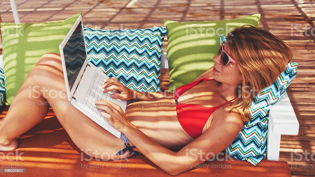 Young woman using the laptop at beach bar stock photo
