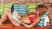 Young woman using the laptop at beach bar