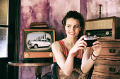 Young woman using vintage camera at home