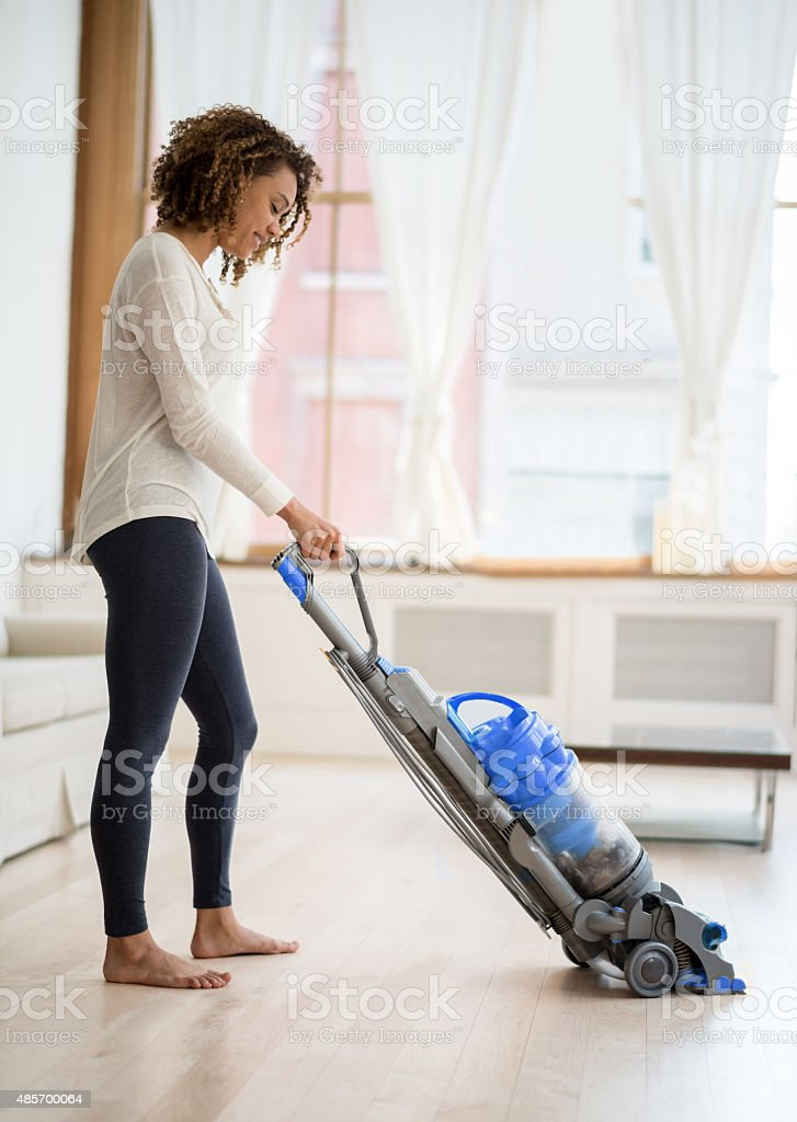 Young woman vacuuming her house stock photo