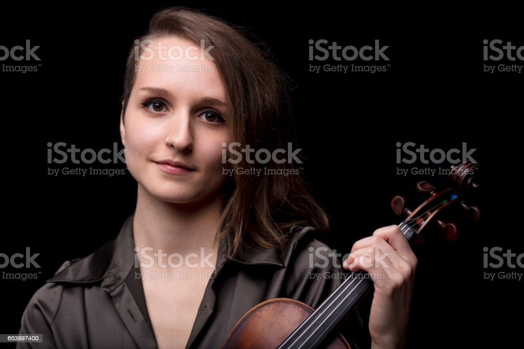 young woman violinist portrait on black stock photo