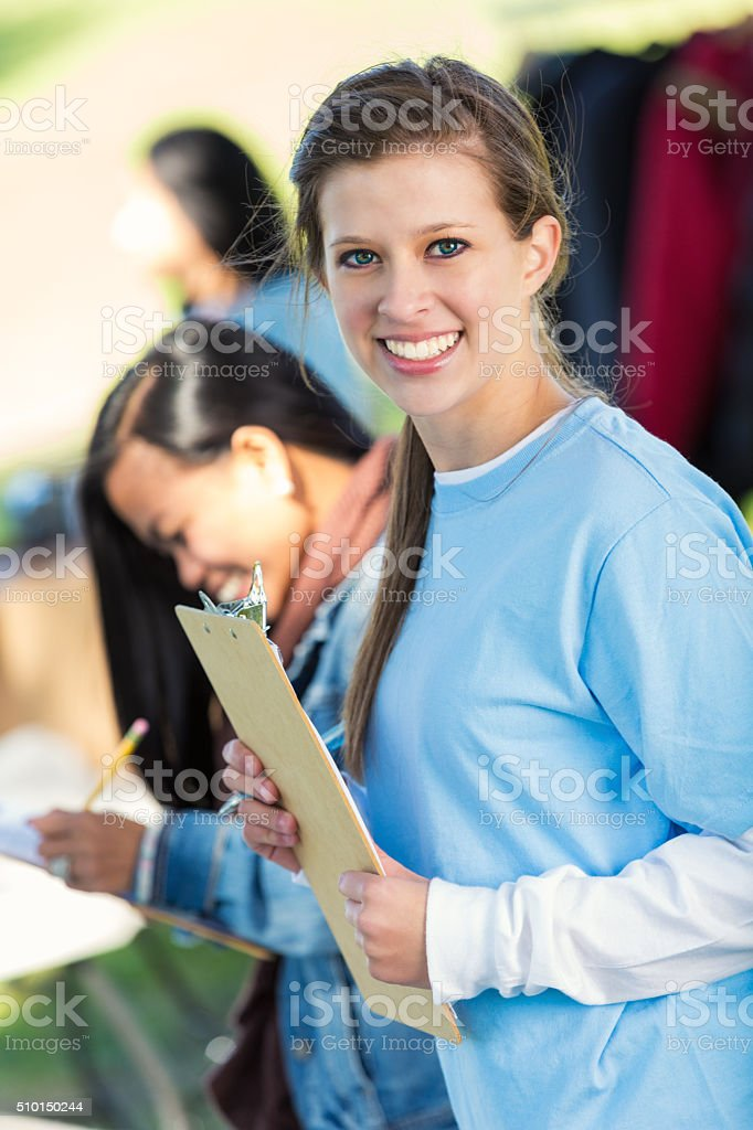 Young woman volunteers at outdoor clothing drive stock photo