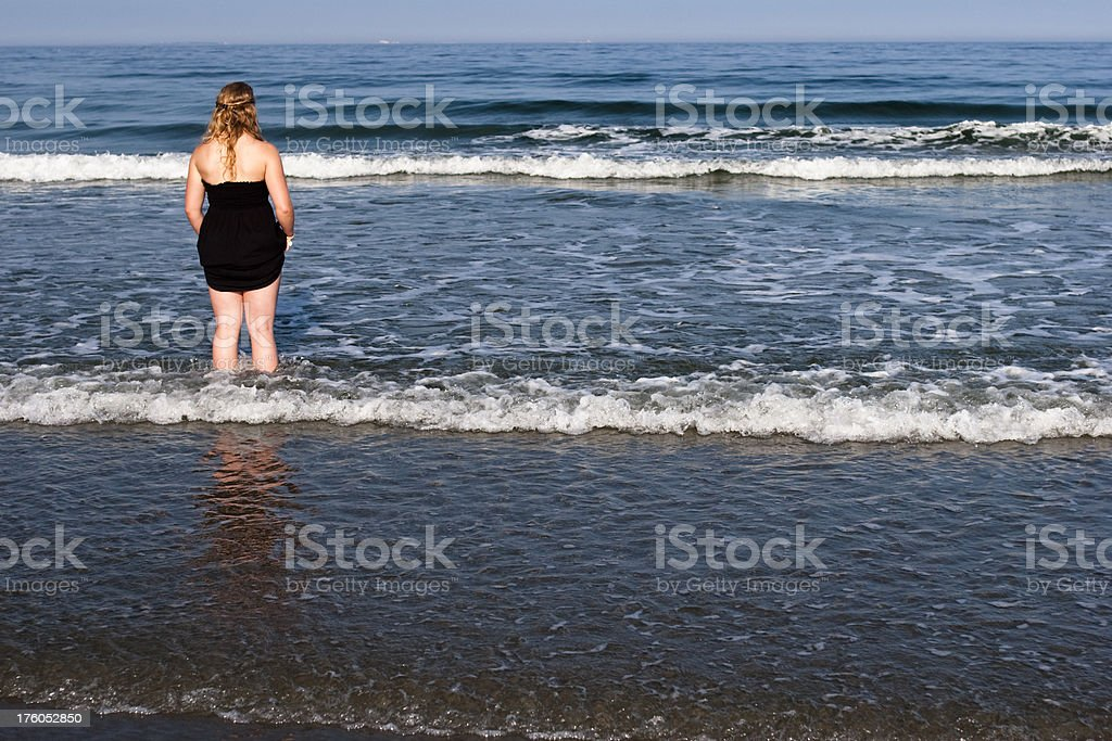Young Woman wading in the ocean at evening. royalty-free stock photo