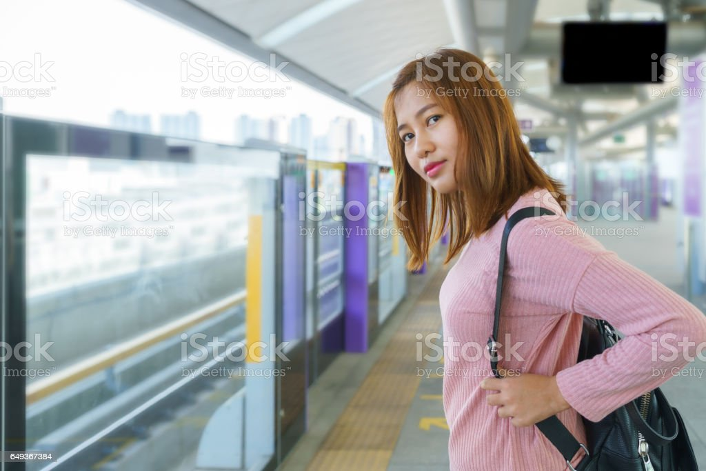 Young woman waiting and looking for sky train in platform stock photo
