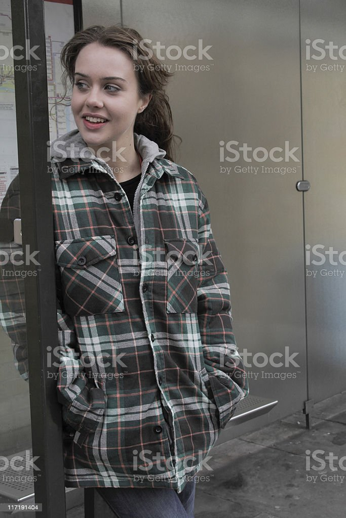 Young woman waiting at bus stop stock photo