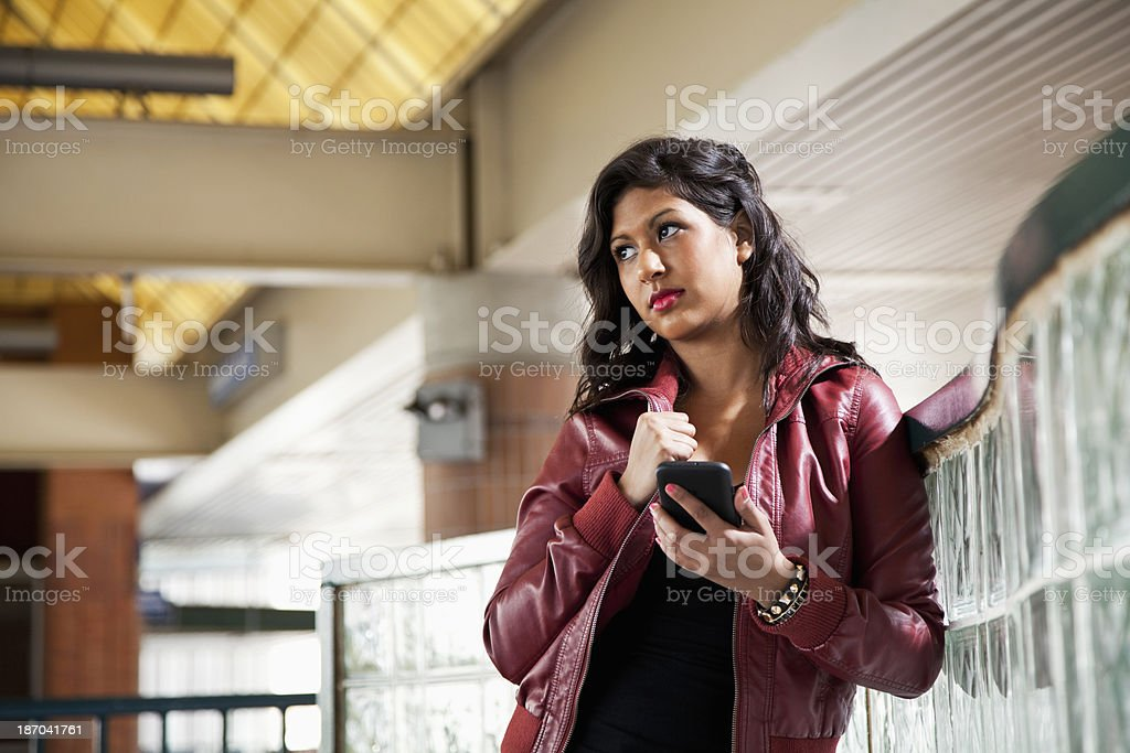 Young woman waiting at train station stock photo