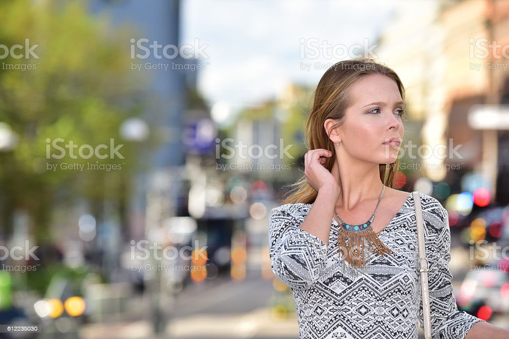 Young woman waiting, central Stockholm, traffic Sveavagen in background stock photo