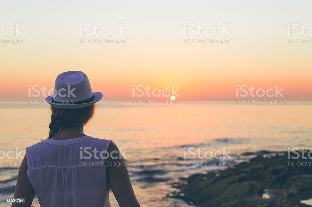 Young woman waiting for sunshine at the beach stock photo