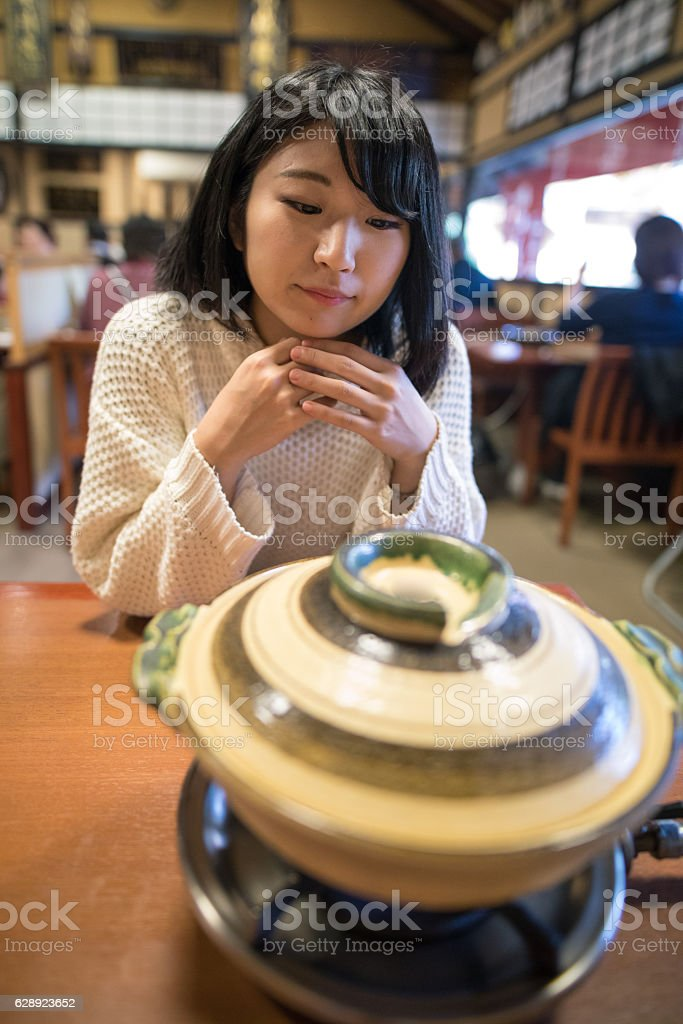 Young woman waiting for tofu in hot pot stock photo