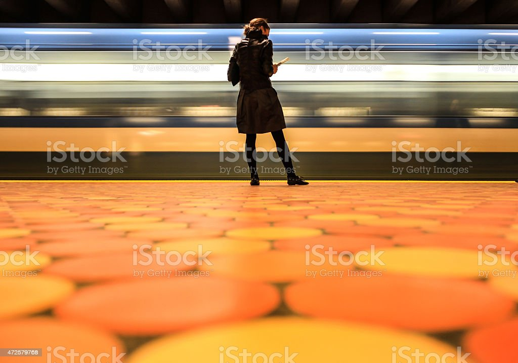 Young woman waiting for train at a subway station stock photo