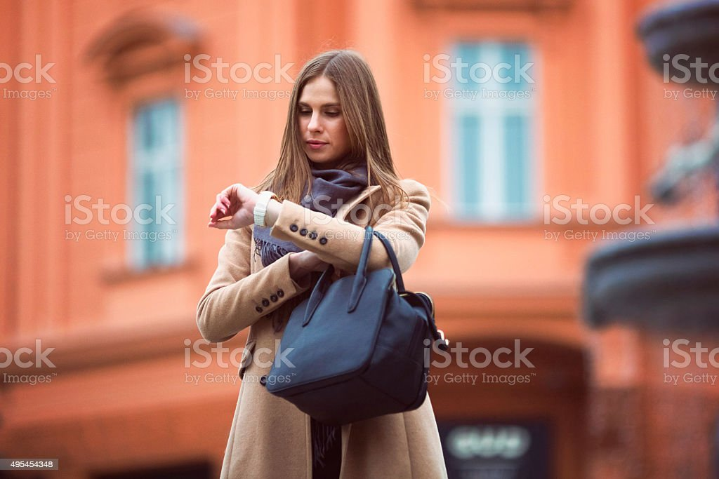 Young woman waiting on the street, stood up stock photo