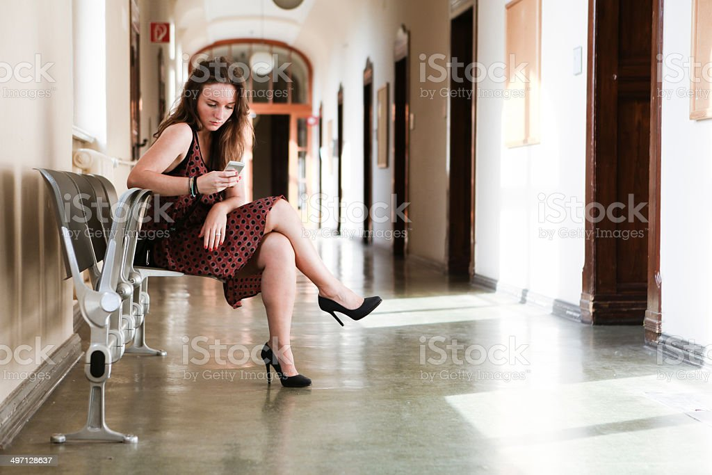 young woman waits in a long empty corridor royalty-free stock photo