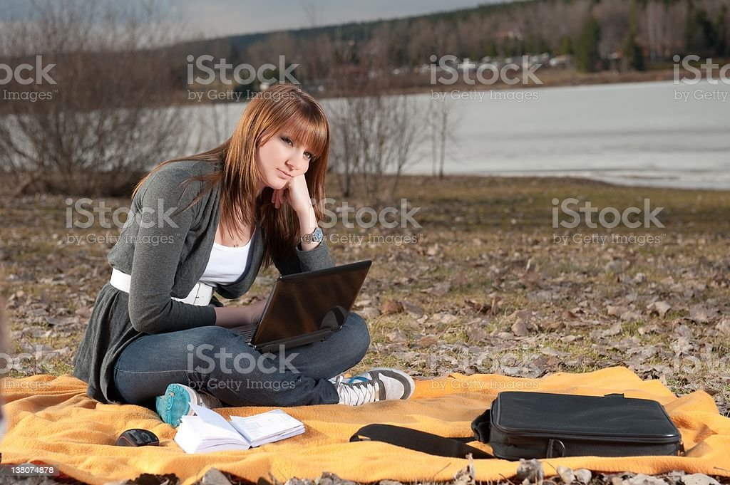 Young woman waits while the laptop loads stock photo