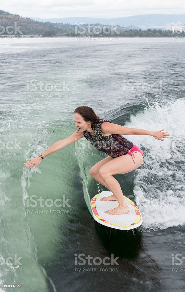 Young woman wakeboarding, wakesurfing, vertical stock photo