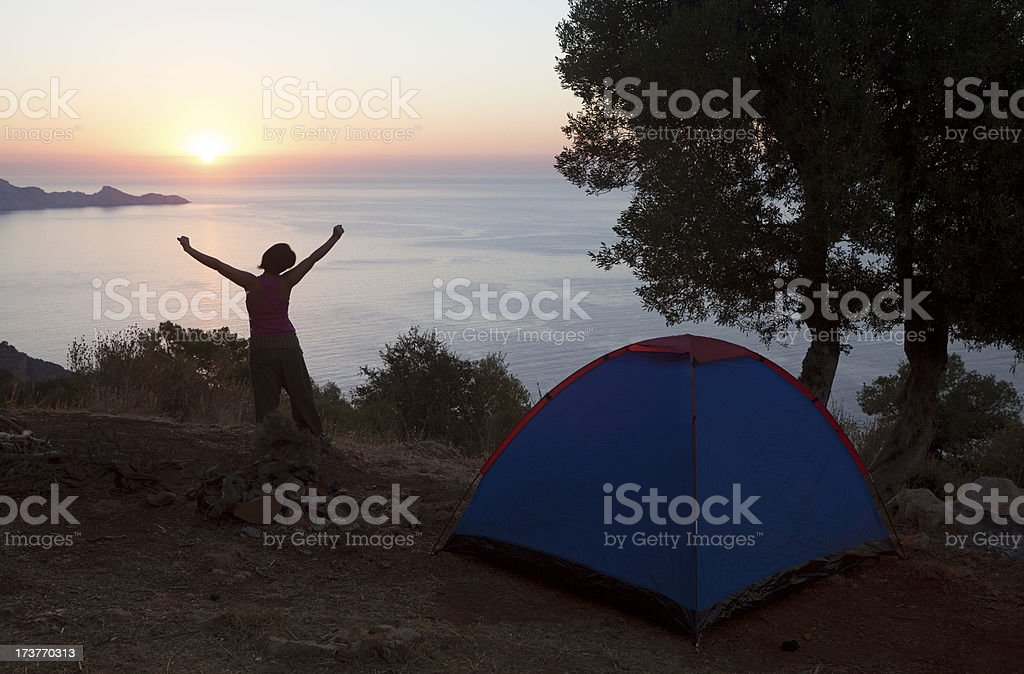 Young woman waking up by camping tent in the morning royalty-free stock photo