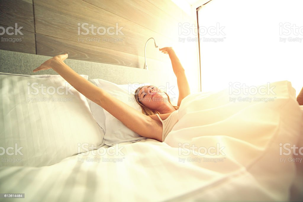 Young woman waking up in her hotel room, stretching arms stock photo