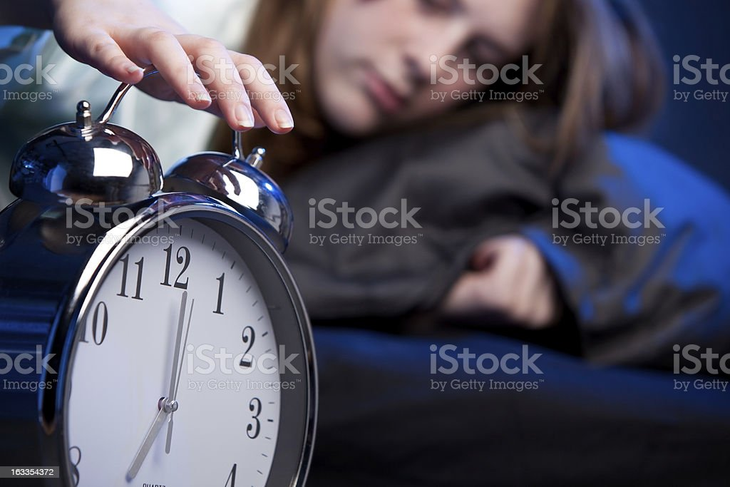 Young woman waking up with alarm clock royalty-free stock photo