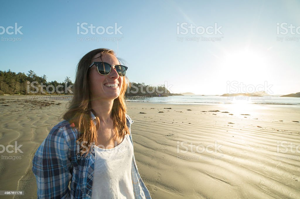 Young woman walking along the beach in Autumn stock photo