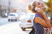 Young woman walking and talking on the mobile phone