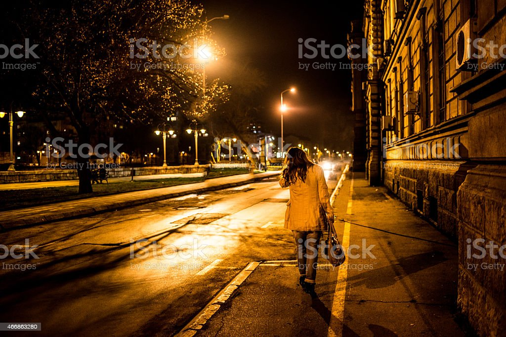 Young woman walking at city in night stock photo