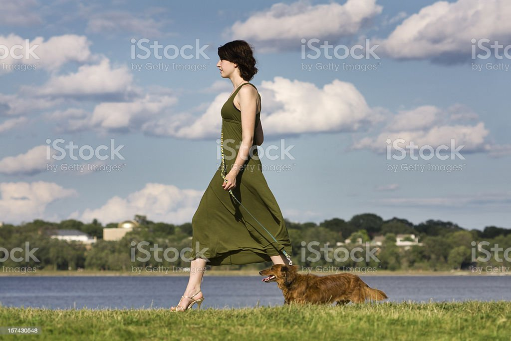 Young Woman Walking Dog Along a Lake royalty-free stock photo