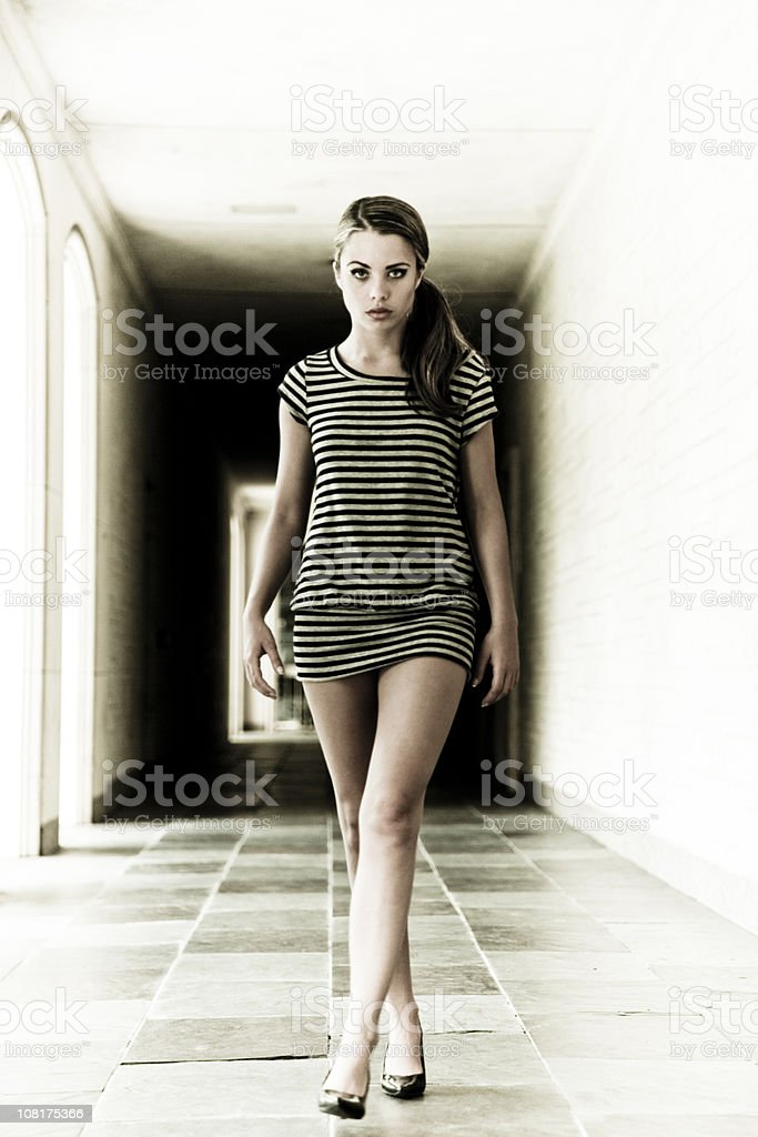 Young Woman Walking Down Hallway royalty-free stock photo