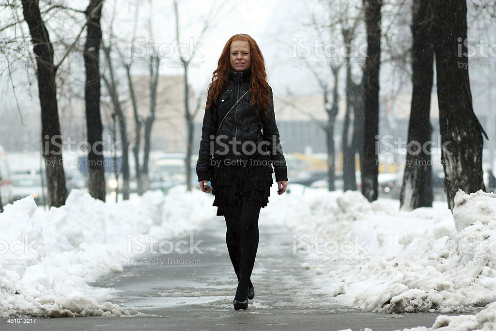 Young woman walking down snow covered street royalty-free stock photo