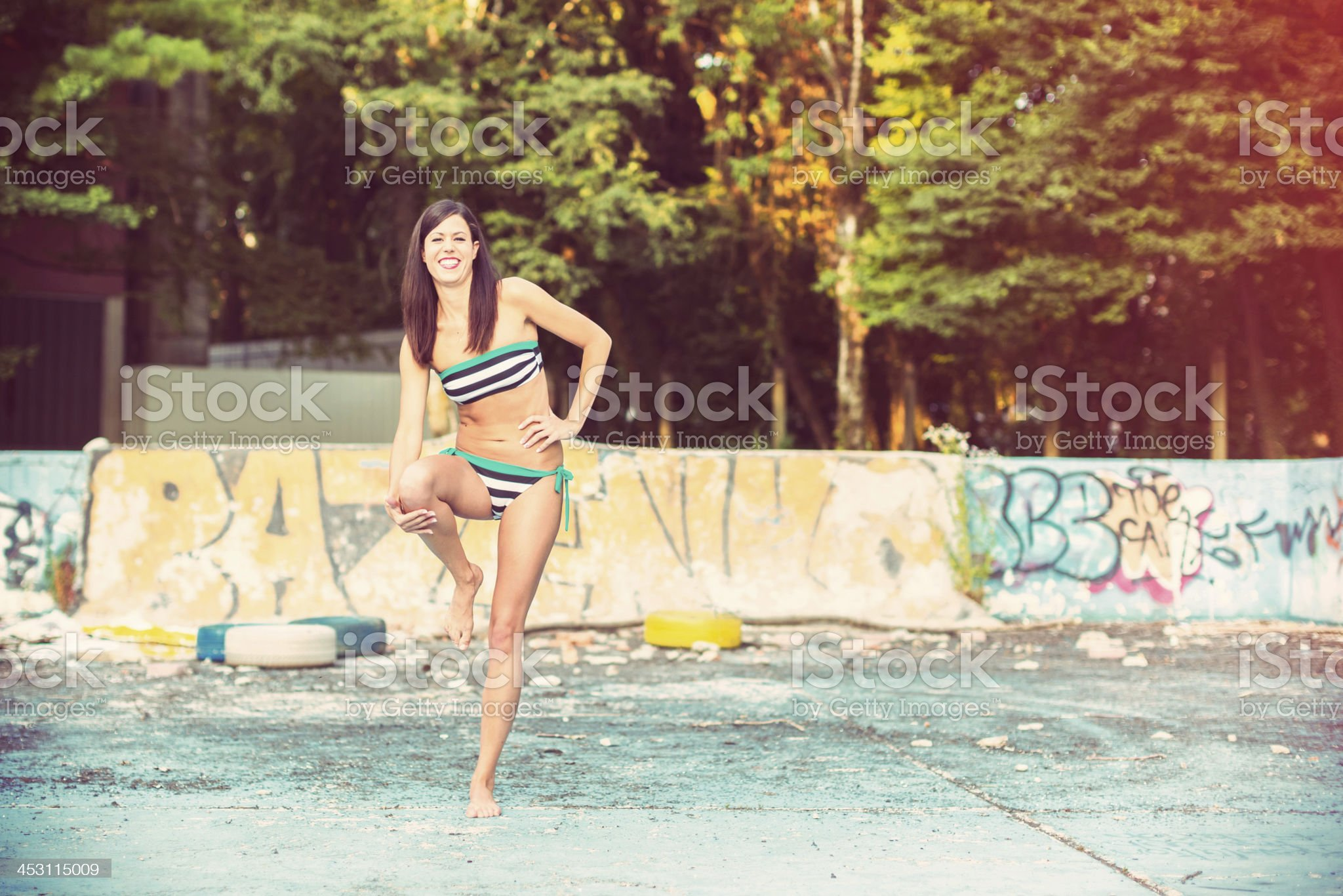 Young woman walking in dirty empty old swimming pool royalty-free stock photo