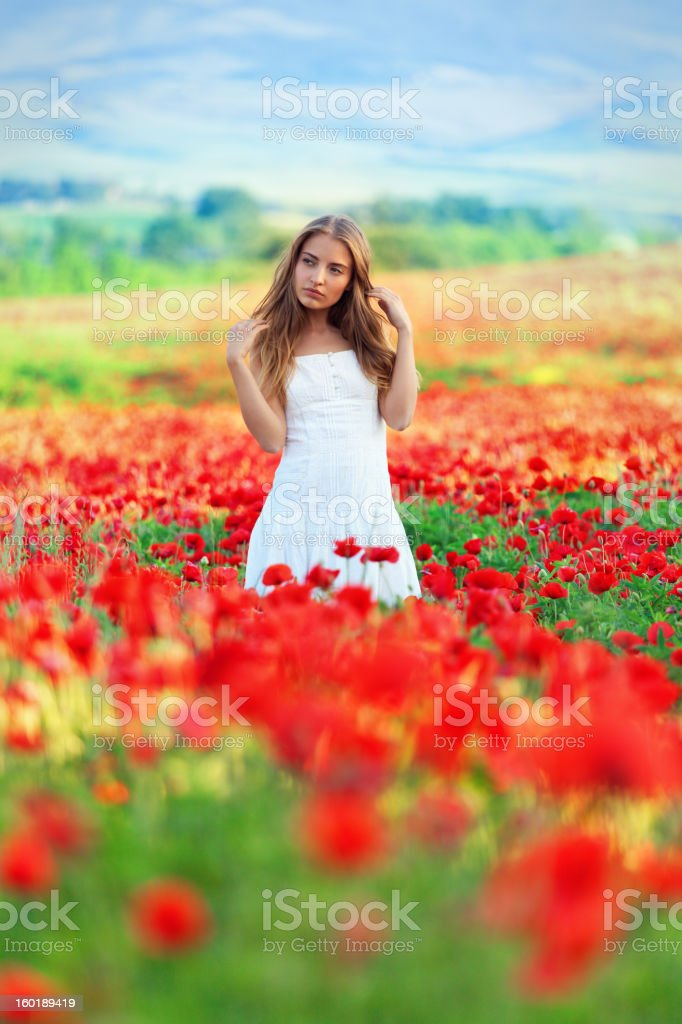 young woman walking in poppy field royalty-free stock photo