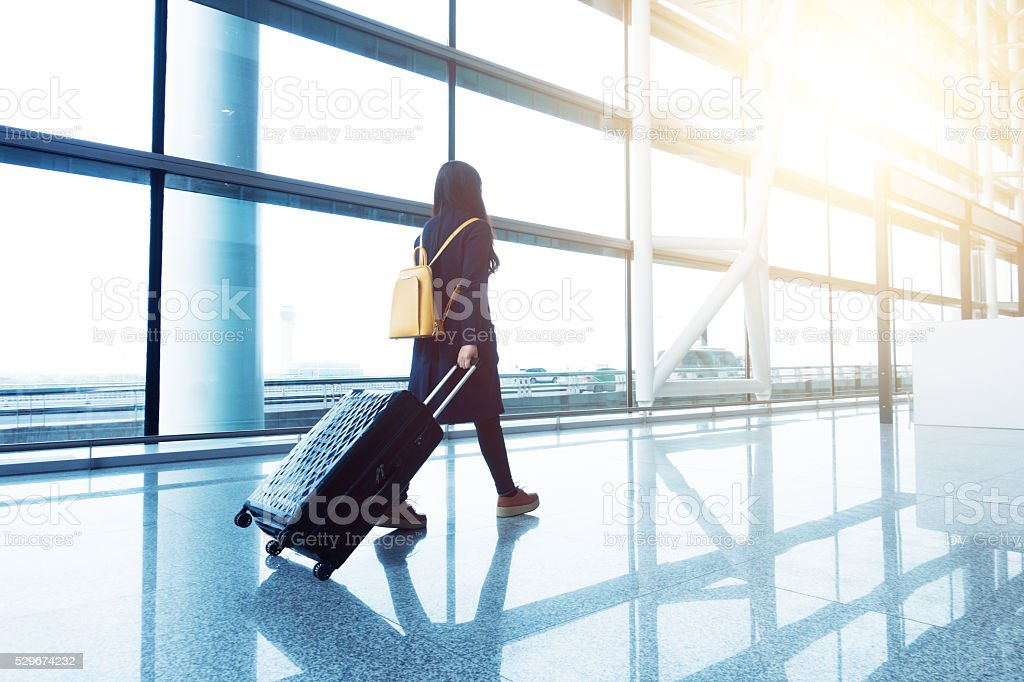 Young woman walking in the airport with luggage. stock photo