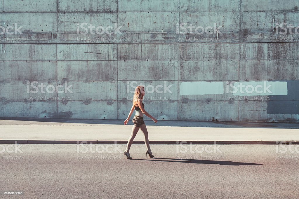 Young woman walking in the city street stock photo