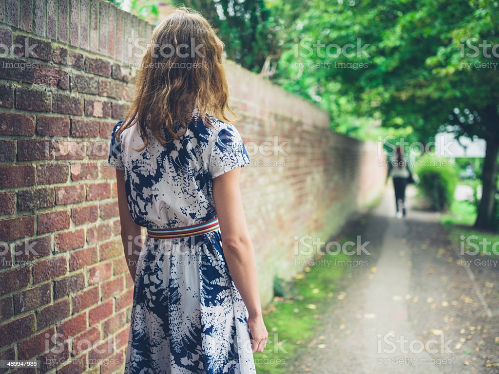 Young woman walking in the street by wall stock photo