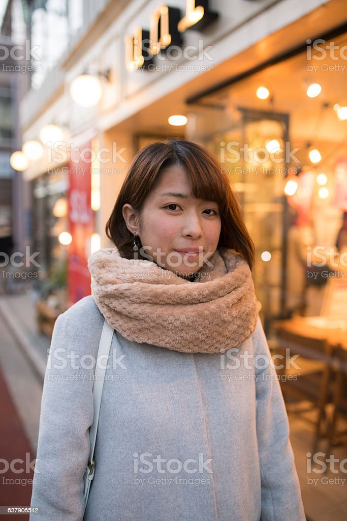 Young woman walking in town in the evening stock photo