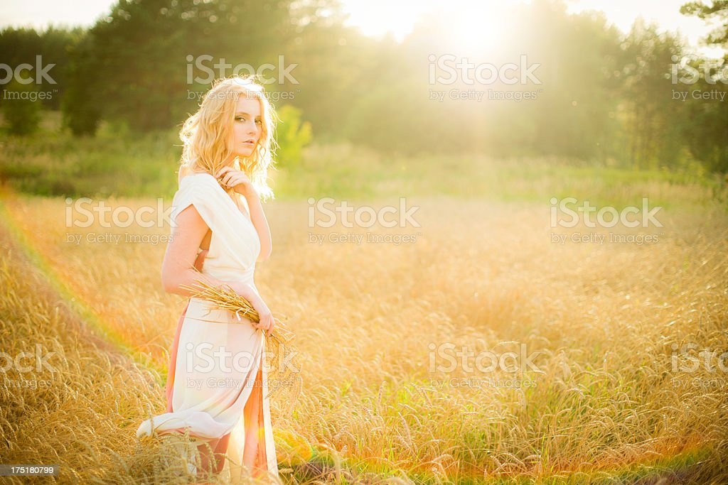 Young woman walking in wheat field royalty-free stock photo