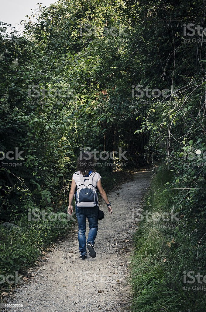 young woman walking into the forest on dirt path stock photo