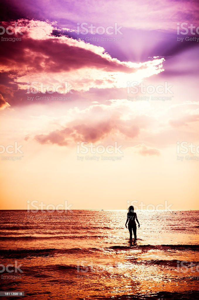 Young woman walking into the sea against sunset royalty-free stock photo