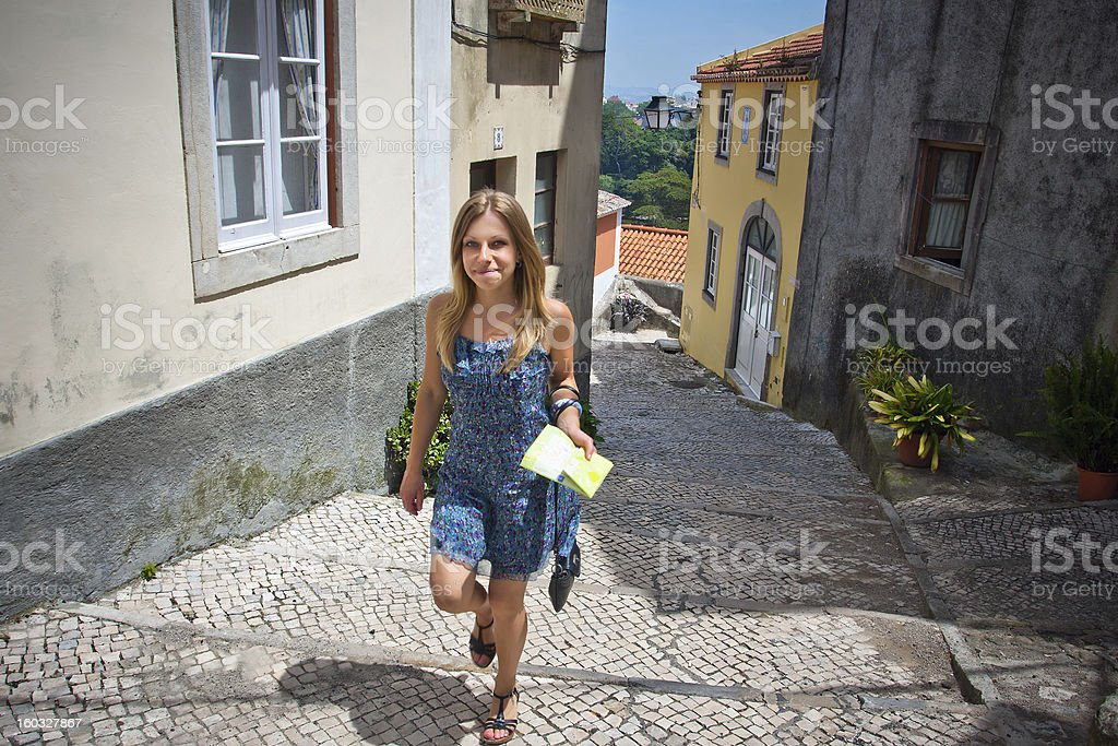 Young woman walking on a cobblestone street in Lisbon royalty-free stock photo