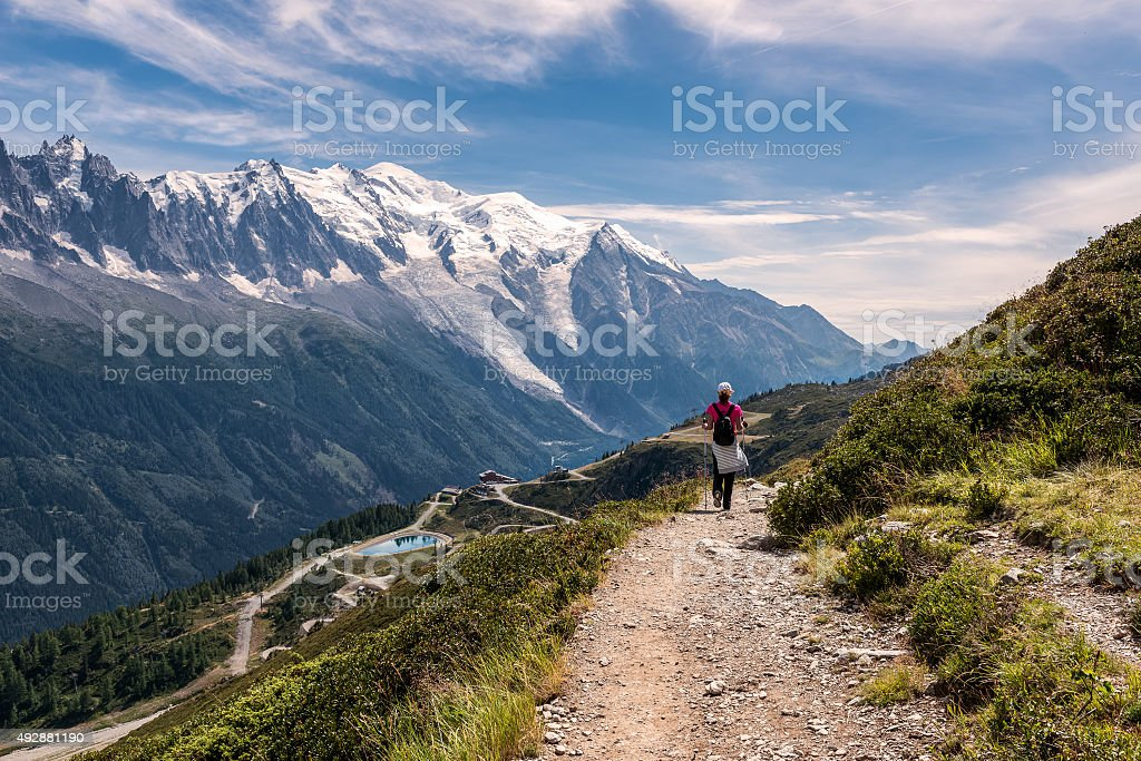 Young woman walking on a footpath in the mountains stock photo