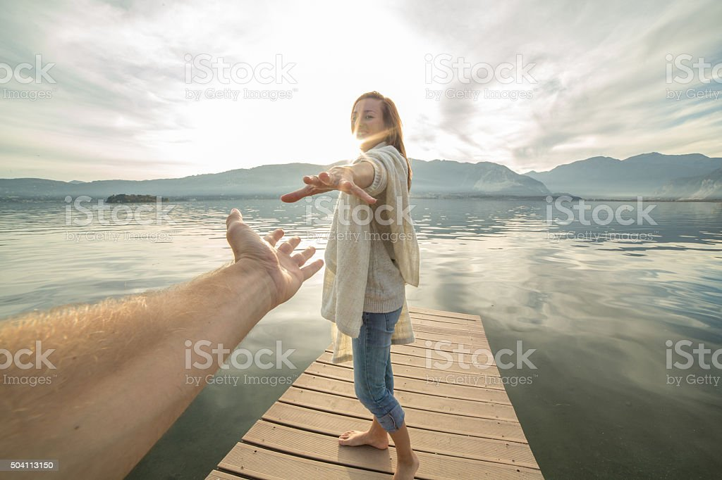 Young woman walking on a jetty holding a man's hand. stock photo