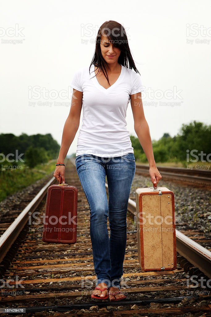 Young woman walking on a railroad track with two suitcases royalty-free stock photo